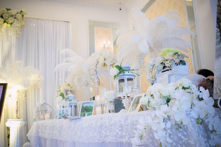 Kết hợp trang trí hoa với khung ảnh giúp không gian phòng cưới thêm phần sinh động